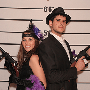 Baltimore Murder Mystery party guests pose for mugshots